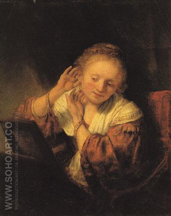 A Young Woman Trying on Earrings 1657 - Rembrandt Van Rijn reproduction oil painting